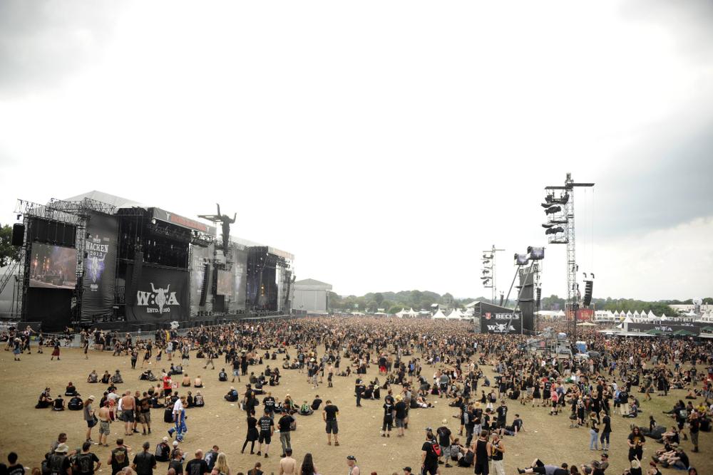 Festivalområde med enorme høytalerrigger og svartkledde mennesker.