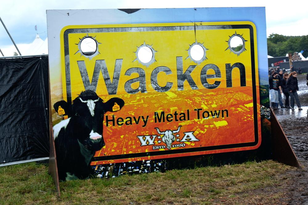 Stort orange skilt med enorme kulehull i: Wacken, Heavy Metall Town.