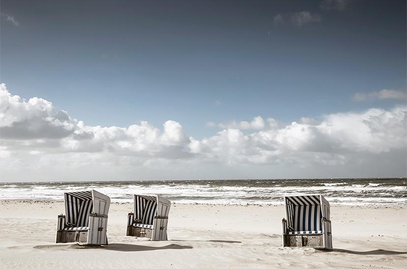 Sandstrand med tre blå- og hvit-stripete, doble strandstoler med vegger og tak.