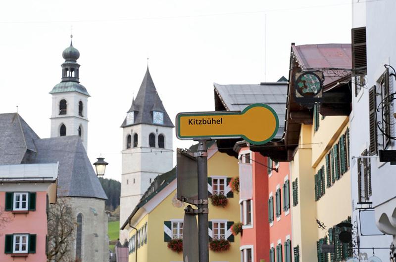 Kitzbühel på et skilt. Fargerike gamle hus og en kirke i bakgrunnen.