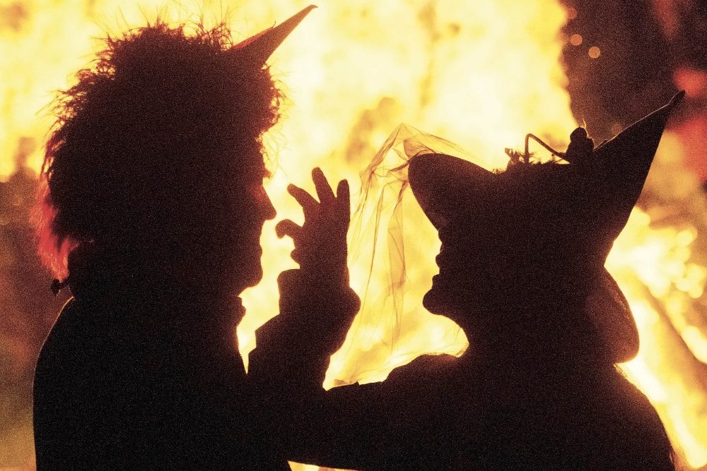 Siluett av to personer foran et bål, utkledd som heks og djevel: Blocksberg