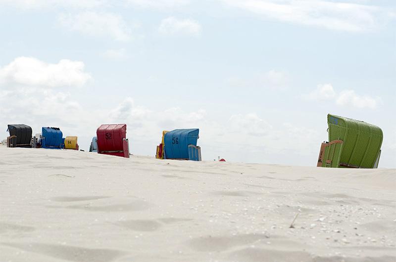 Sandstrand med fargerike, doble strandstoler med vegger og tak.