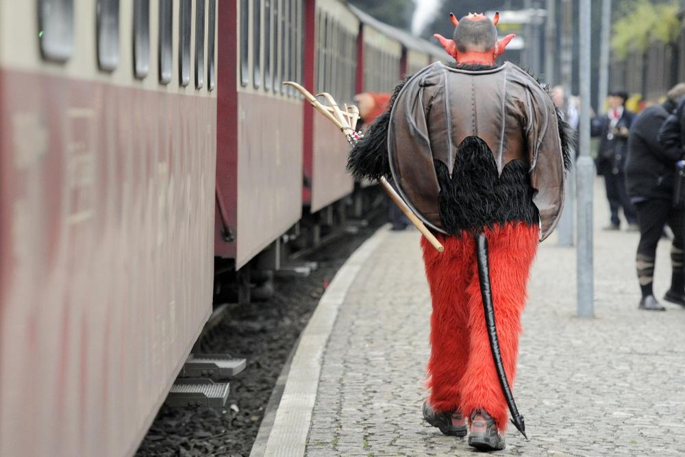 Mann i djevelkostyme på en togperrong: Blocksberg.
