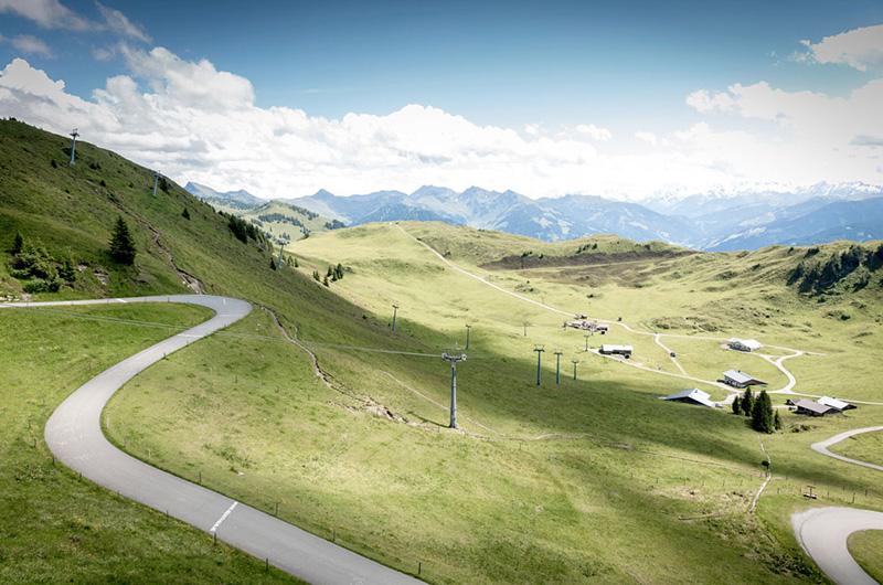 Snirklete vei oppover grønnkledd fjellside, med små hytter.