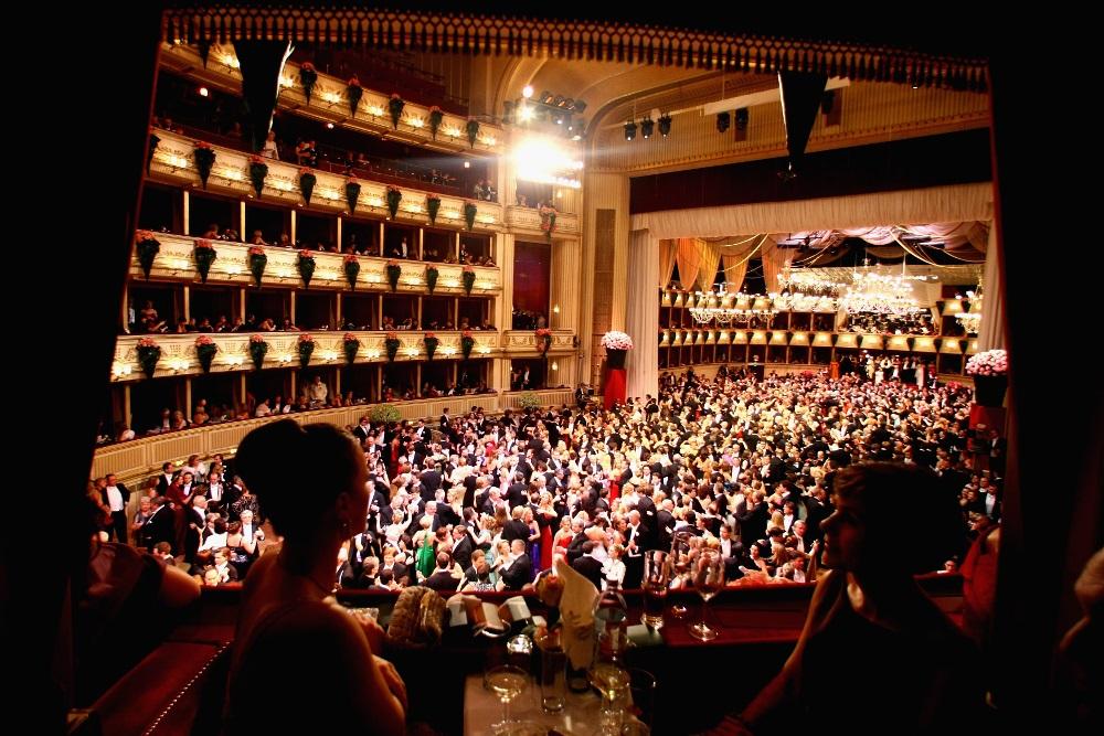 Utsikt fra en balkong ned mot en dansende folkemengde i et festpyntet lokale: Wiener Opernball.