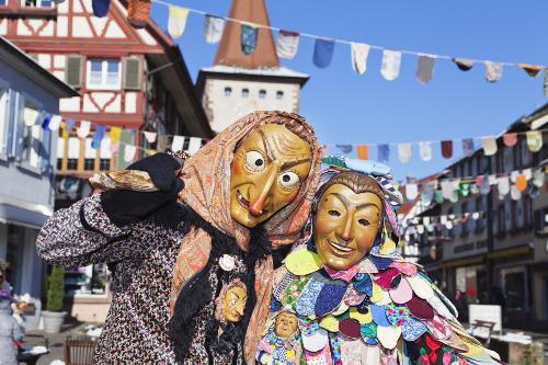 To maskekledde mennesker i en gate med bindingsverkshus: Karneval i Köln.