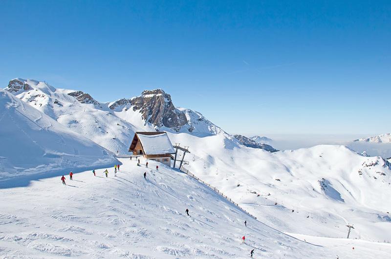 Skiheis med hus på toppen. Alpene i bakgrunnen, Folk på ski i forgrunnen.