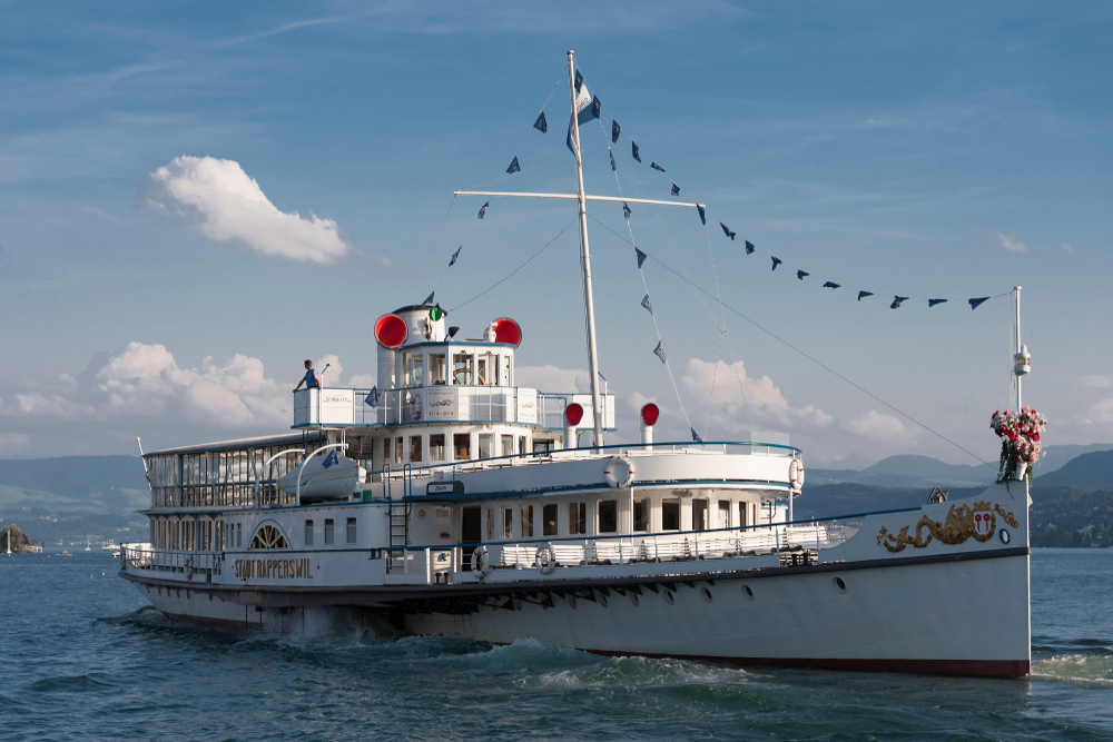 Gammel hvit hjuldamper og restaurantbåt.