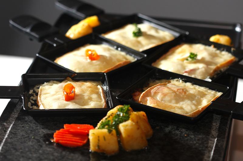 Smeltet ost i svarte metallformer, og stekte grønnsaker: Raclette.