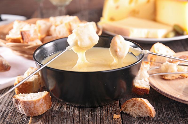 Brødbiter på spidd dyppes i smeltet ost: Fondue.
