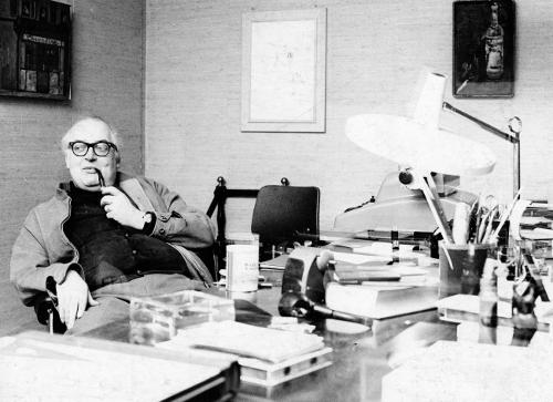 Eldre mann med briller og pipe, i en stol ved et fullt skrivebord: Friedrich Dürrenmatt.