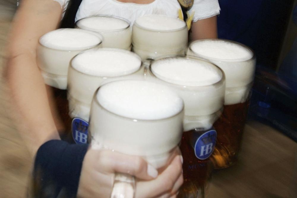 En kvinnelig kelner med rundt ti litersglass med øl i en tysk ølhall. Høyt under taket og dekorert med lyslenker.