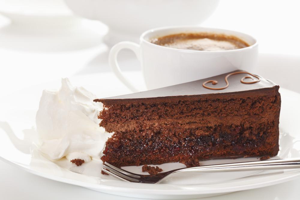 Brun kake med hvite lag på et utendørs cafébord: Sachertorte.
