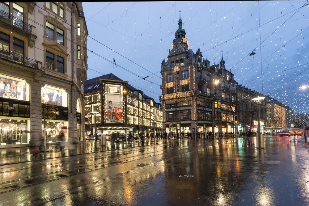 Regnvåt bygate med butikker og neonlys: Bahnhofstrasse i Zürich